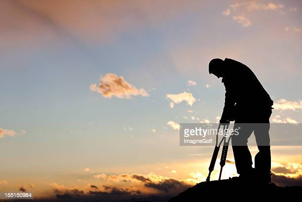 silhouette of a sad injured man with crutches - man crutches stock photos and pictures