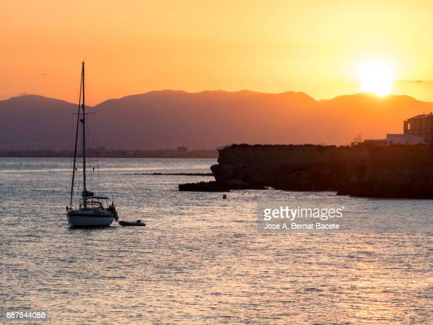 Silhouette of a sailboat in the sea near a harbor, during a sunset between the mountains on the island of Tabarca