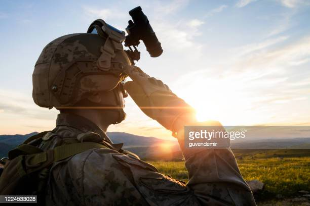 silhouette of a saluting solider  against sunset sky - saluting stock pictures, royalty-free photos & images