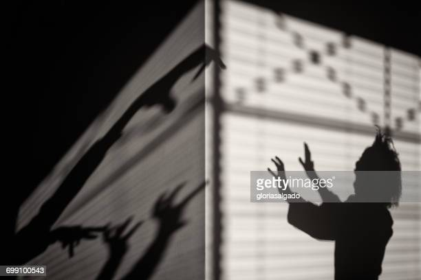 Silhouette of a scared girl with shadow monsters
