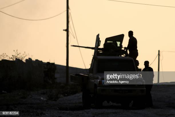 Silhouette of a soldier aiming with a gun loaded on back of a vehicle is seen after Free Syrian Army and Turkish Army liberate the village of Qatma...