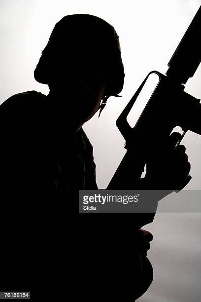 silhouette of a soldier holding a gun - terrorism stock pictures, royalty-free photos & images