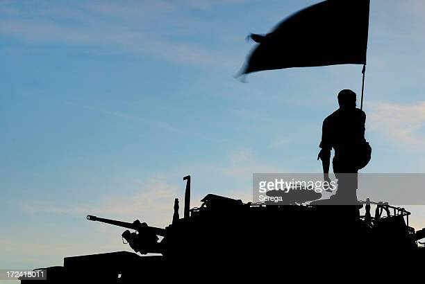 Silhouette of a soldier with a flag on a tank