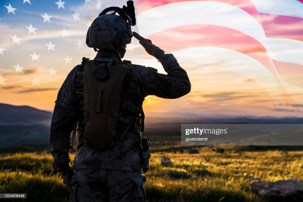 Silhouette Of A Solider Saluting Against US Flag at Sunrise : Stock Photo
