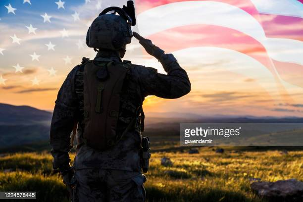 silhouette of a solider saluting against us flag at sunrise - army soldier stock pictures, royalty-free photos & images