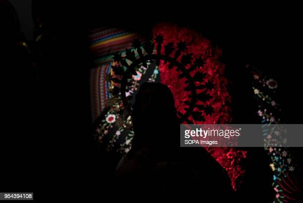 Silhouette of a statue in front of a cross decorated with carnations of Comendadoras de Santiago convent seen the day before the Dia de las Cruces El...