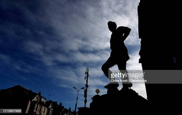 A silhouette of a statue of Jonny Hayes outside of Craven Cottage home of Fulham FC is seen as football in England remains suspended due to Covid19...