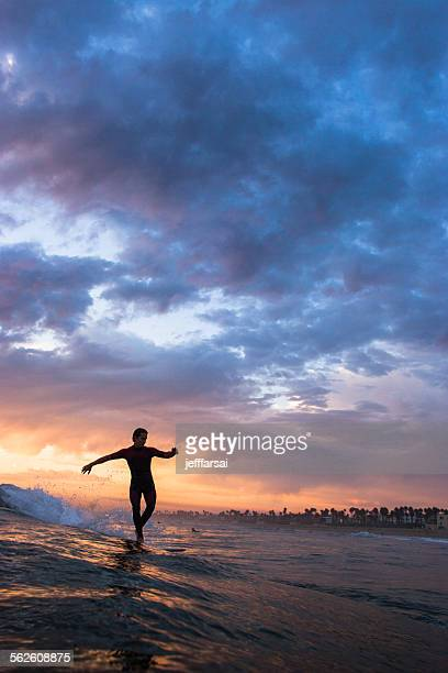 Silhouette of a surfer walking to the nose of his longboard at sunset, california, usa