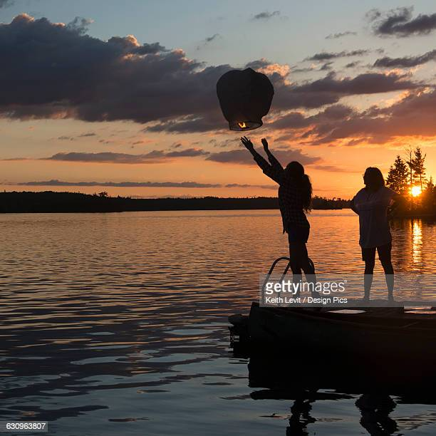 Silhouette of a teenage girl releasing a lit lantern out over a lake at sunset
