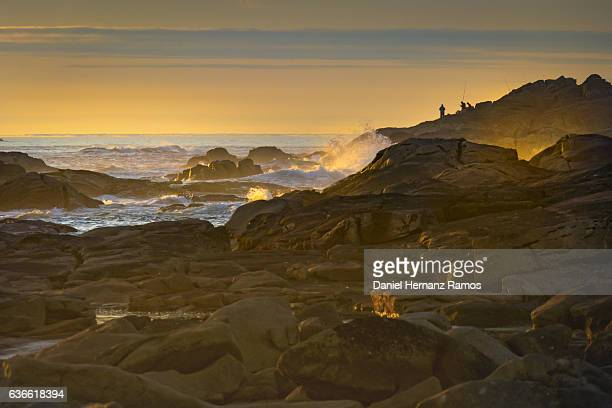 Silhouette of a three fishermen on the rock at sunset. La Guardia, Galicia. Spain