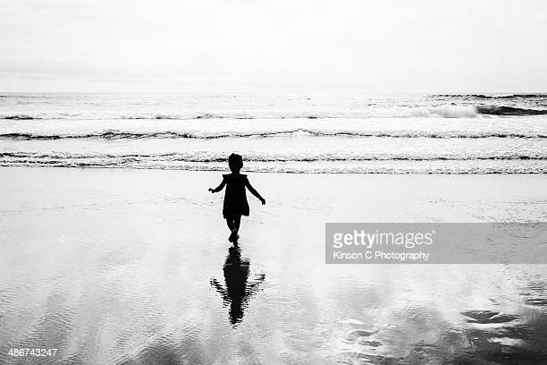 Silhouette of a toddler running to the beach