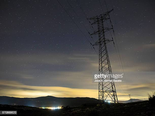 silhouette of a tower of high tension on a mountain in the night, with the lights of a people in the bottom - big bottom stock pictures, royalty-free photos & images