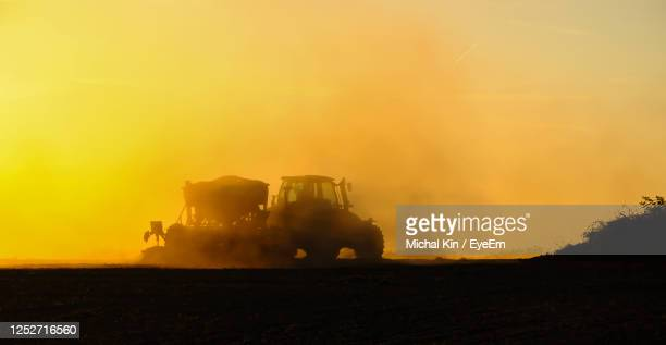 silhouette of a tractor sowing seeds in a field in a cloud of dust against the background. - 農業機械 ストックフォトと画像