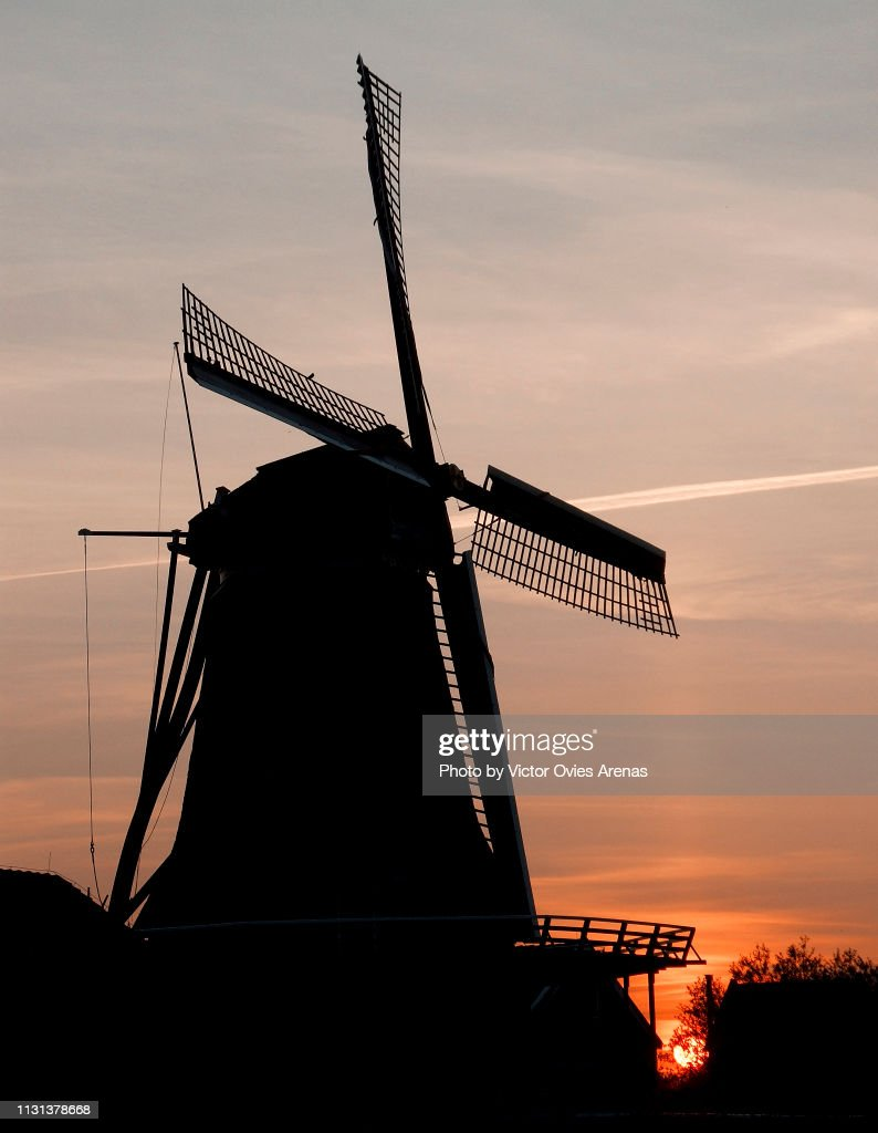 Silhouette of a traditional Dutch windmill backlighted at sunset in Zaanse Schans, Netherlands : Foto de stock