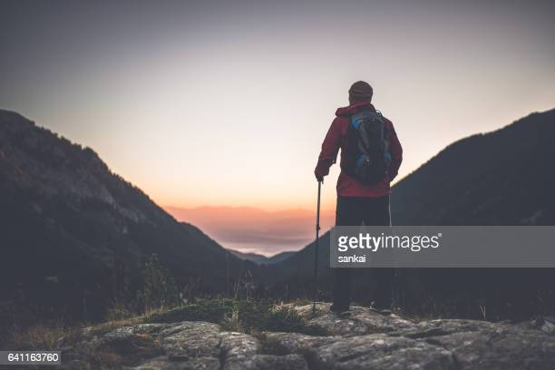 Silhouette of a traveler on the top of the mountain to meet the dawn