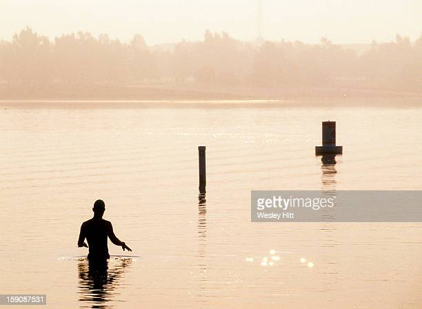Silhouette of a triathlete in the water warming up