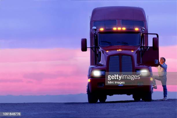 a silhouette of a truck driver getting into the cab of his commercial class 8 truck tractor at sunrise. - vehicle light stock photos and pictures