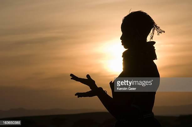 Silhouette of a Turkana girl talking with her hands, Loigyalani, Northern Kenya.