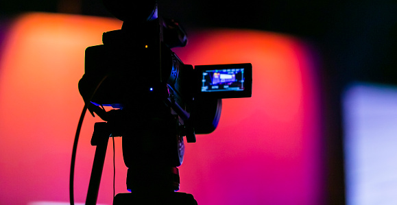 Silhouette of a TV Camera filming a live broadcast 1090034098