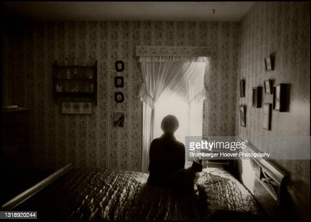 Silhouette of a woman and a cat sitting on a bed, Hayward, California, 1984.