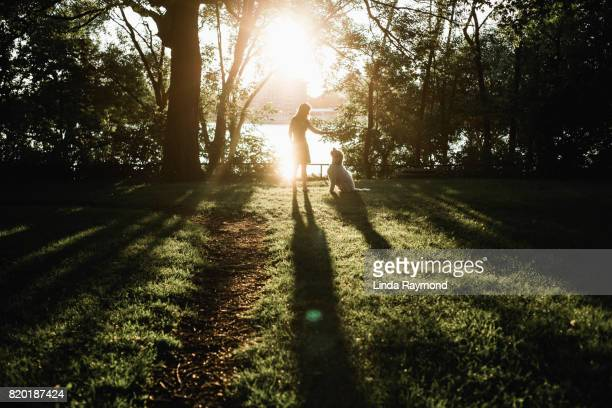 Silhouette of a woman and a dog looking at each other at sunset