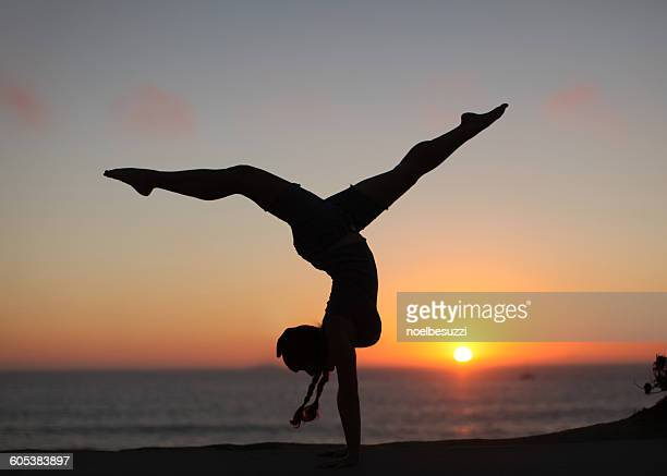 Silhouette of a Woman doing handstand with legs apart on the beach