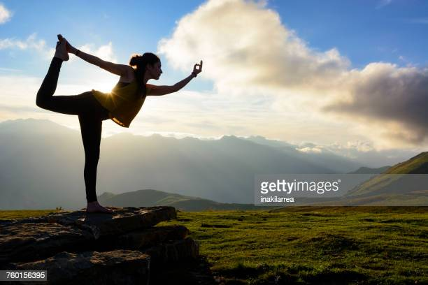 Silhouette of a woman doing standing bow pulling pose in mountains, Col dAubisque, Pyrenees, France