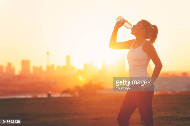 silhouette of a woman drinking form a cold water bottle. - bere foto e immagini stock