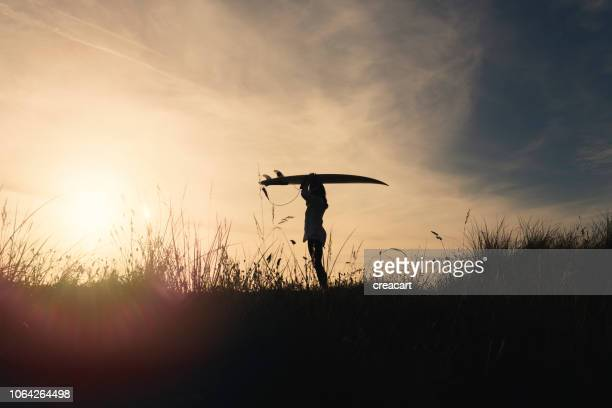 silhouette of a woman holding a surfboard above her head at sunset, gwithian towan beach, cornwall. - june stock pictures, royalty-free photos & images