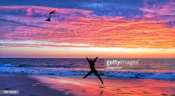 Silhouette of a woman Jumping on the beach at sunset, Australia