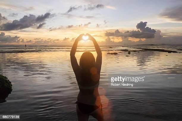 Silhouette of a woman making heart shape at sunset over ocean, Uluwatu, Bali, Indonesia