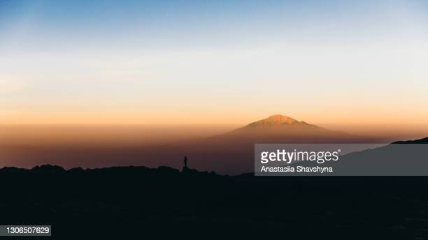 silhouette of a woman meeting the magical sunrise staying on the top of the mountain - human arm stock pictures, royalty-free photos & images