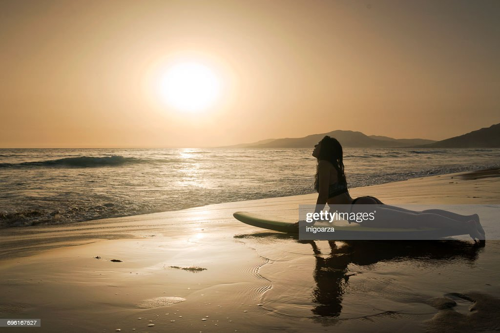 Silhouette Of A Woman On A Surfboard Doing Cobra Yoga Pose