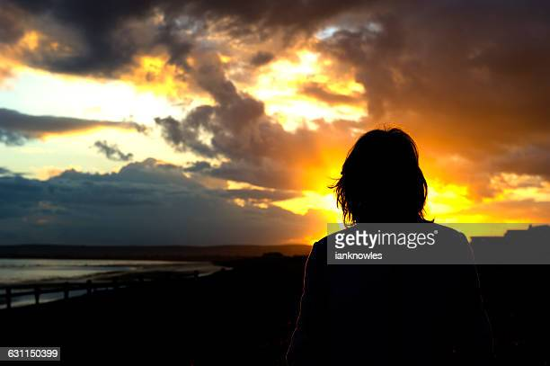 Silhouette of a woman on beach at sunset, Normans Bay, East Sussex, England, UK