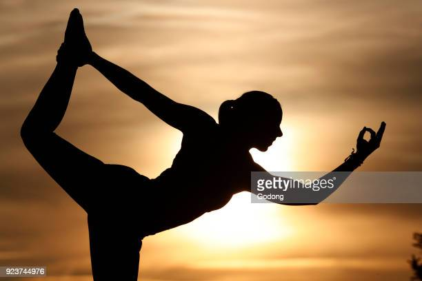 Silhouette of a woman practicing yoga against the light of the evening sun Natarajasana Lord of the Dance French Alps France