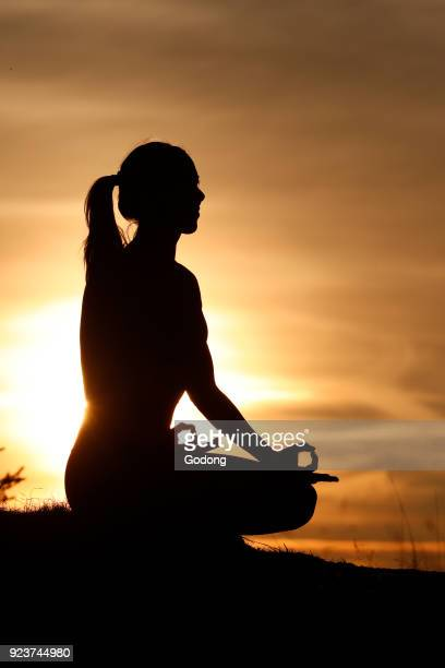 Silhouette of a woman practicing yoga against the light of the evening sun Lotus position French Alps France