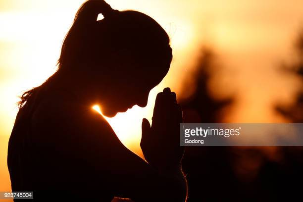 Silhouette of a woman practicing yoga against the light of the evening sun French Alps France