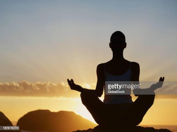 Silhouette d'une femme pratiquant yoga au lever du soleil
