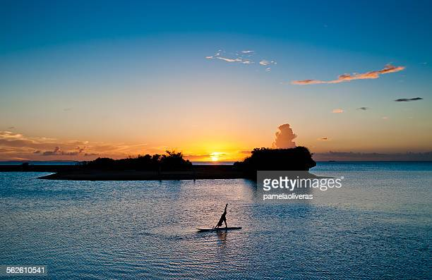 Silhouette of a woman practicing yoga on a paddleboard, Japan