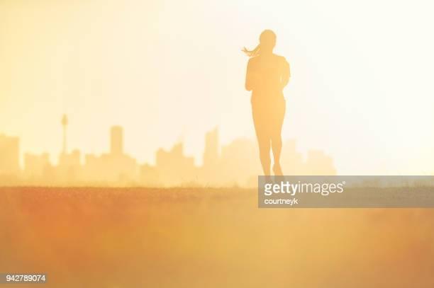 Silhouette d'une femme qui court dans le parc.