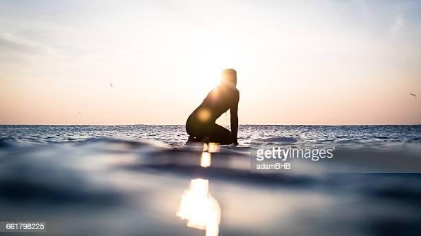 Silhouette of a woman sitting on surfboard in ocean, Malibu, california, america, USA