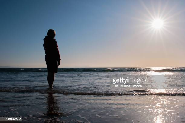 silhouette of a woman standing on the beach looking over the atlantic ocean in the sunset - finn bjurvoll stock pictures, royalty-free photos & images
