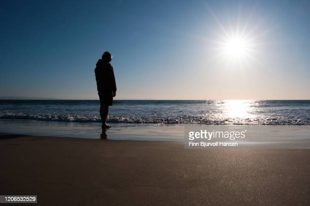 silhouette of a woman standing on the beach looking over the atlantic ocean in the sunset - finn bjurvoll - fotografias e filmes do acervo