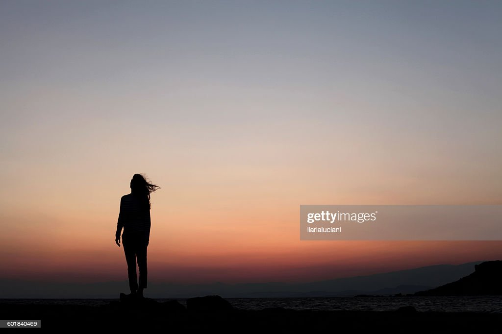 Silhouette of a woman standing outdoors at sunset : Stock Photo