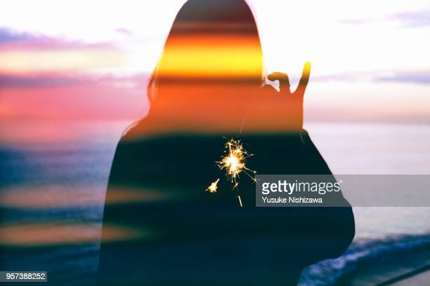 Silhouette of a woman wearing fireworks