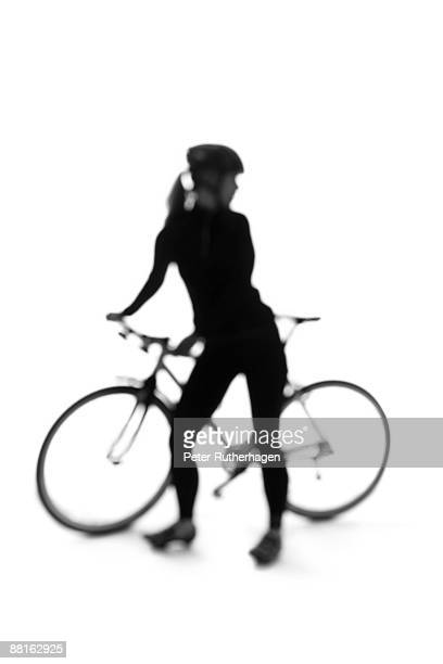 Silhouette of a woman with a bicycle.