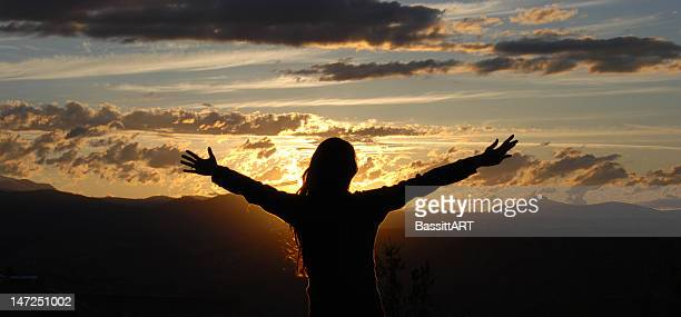 A silhouette of a woman with her arms open in the sunset