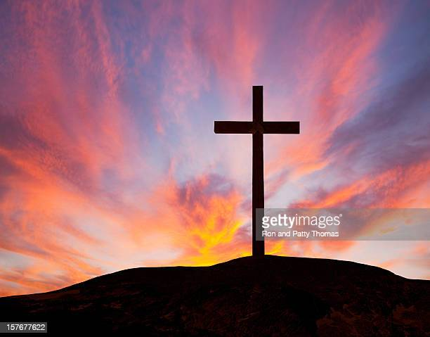 Silhouette of a wooden cross on a hill with a sunset