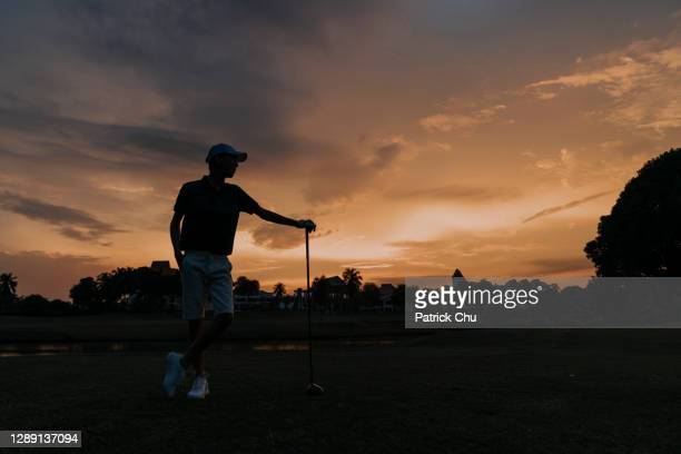 silhouette of a young asian chinese man golfer holding golf club at golf course during sunset - twilight stock pictures, royalty-free photos & images