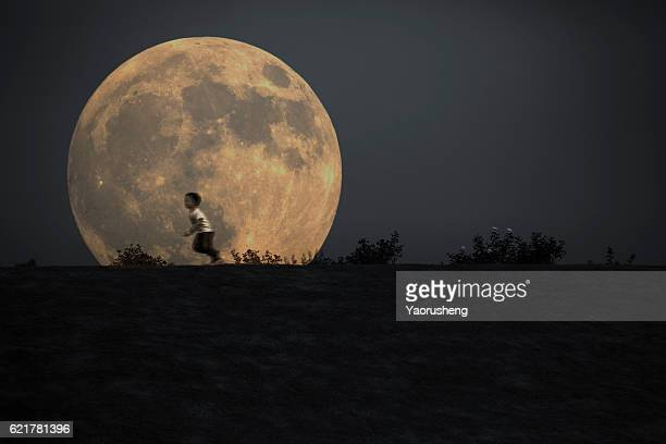 silhouette of a young boy running in front of the full moon - mini moon stock pictures, royalty-free photos & images